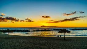 Zonsondergang over de lagune en het strand met met stro bedekte paraplu's onder blauwe hemel op de Westkust van Oahu royalty-vrije stock foto