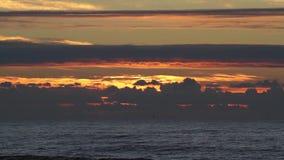 Zonsondergang over de oceaan met kleine golven, wolken en mooie rode zonlicht en bezinningen over de waterspiegel stock videobeelden