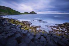 Zonsondergang over de Reuze` s Verhoogde weg van de rotsenvorming, Provincie Antrim, Noord-Ierland, het UK Stock Afbeeldingen