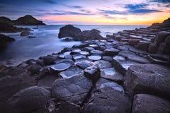 Zonsondergang over de Reuzenverhoogde weg van de rotsenvorming, Provincie Antrim, Noord-Ierland, het UK Royalty-vrije Stock Foto