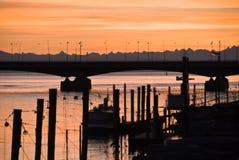 Zonsondergang over de rivierbrug van Rijn Stock Foto