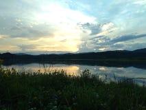 Zonsondergang over de rivieroever stock foto's