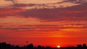 Zonsondergang over de silhouetten van gebouwen in de stads tijd-tijdspanne stock video