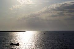 Zonsondergang over de stadsbaai met boten en pijler op de achtergrond stock fotografie