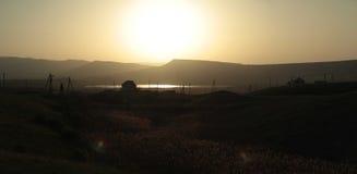 Zonsondergang over de vallei met een huis en een meer Stock Foto