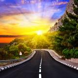 Zonsondergang over de weg Stock Afbeeldingen