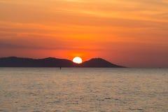 Zonsondergang over de zeekust achter de berg stock fotografie