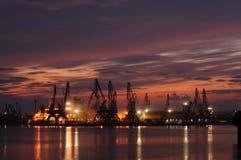 Zonsondergang over een de industriehaven met kranen in Bulgarije, Varna stock afbeeldingen