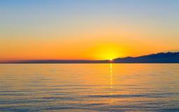 Zonsondergang over een meer door bergen wordt omringd die Royalty-vrije Stock Afbeelding