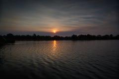 Zonsondergang over een meer met eenden en vogels royalty-vrije stock foto's