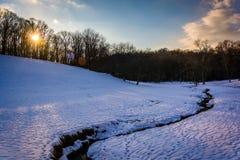 Zonsondergang over een stroom op een snow-covered gebied in landelijk Baltimore royalty-vrije stock foto's