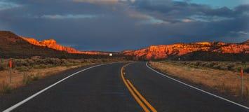 Zonsondergang over een woestijnweg Stock Foto