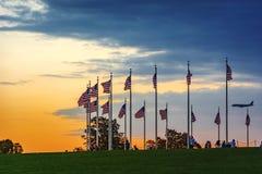Zonsondergang over golvende Amerikaanse vlaggen met toeristen en vliegtuig het landen Royalty-vrije Stock Foto's