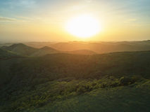 Zonsondergang over groen heuvelslandschap Stock Foto's