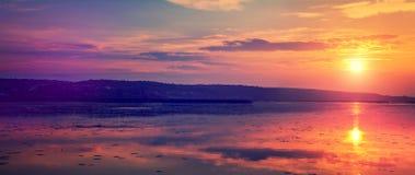Zonsondergang over het meer kleurrijke die wolken in de hemel, in het water wordt weerspiegeld Royalty-vrije Stock Foto