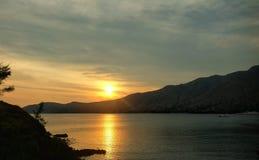 Zonsondergang over het overzees en de berg Stock Foto's