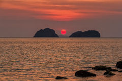 Zonsondergang over het overzees en de zon die in het water tussen de eilanden plaatsen Stock Fotografie