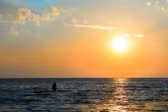 Zonsondergang over het overzees en het silhouet van een mens in de afstand stock fotografie