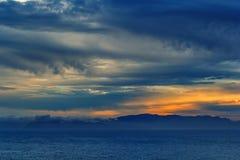 Zonsondergang over het overzees met onweer het naderbij komen Stock Foto's
