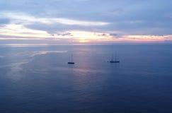 Zonsondergang over het overzees met varende boten Stock Afbeelding