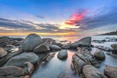 Zonsondergang over het overzees Steen op de voorgrond stock afbeelding