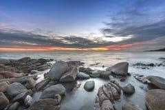 Zonsondergang over het overzees Steen op de voorgrond stock foto's