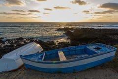 Zonsondergang over het overzeese landschap met oude blauwe houten vissersboot Stock Afbeelding
