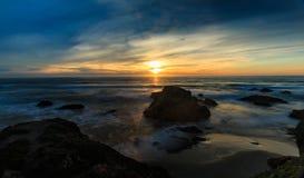 Zonsondergang over het strand met rotsen en schommelende golven stock foto