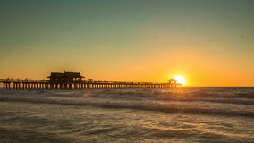 Zonsondergang over horizon en houten pijler van Caraïbisch strand van Napels in Florida stock footage