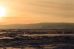 Zonsondergang over ijsoppervlakte van Straat Kleine Overzees van Meer Baikal stock foto's