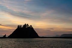 Zonsondergang over kleine eilanden in silhouet stock afbeelding