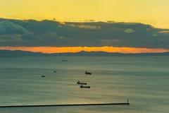 Zonsondergang over kustlijn met vervoerschip Stock Foto