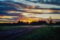 Zonsondergang over landelijke weg Stock Foto