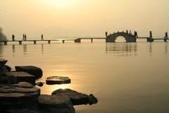 Zonsondergang over meer en brug Stock Fotografie