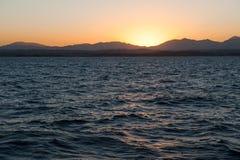 Zonsondergang over overzees en bergen Stock Afbeeldingen