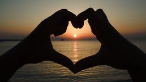 Zonsondergang over overzees in hart van handen wordt gemaakt die stock videobeelden