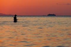 Zonsondergang over overzees, visser zich in water bevinden en varende schipachtergrond die op een tropisch eiland Royalty-vrije Stock Afbeelding