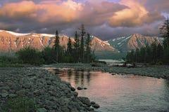 Zonsondergang over rivier en bergen Stock Foto's