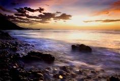 Zonsondergang over rotsachtige kust Stock Foto