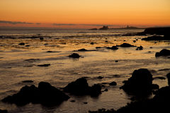 Zonsondergang over rotsachtige kustlijn Royalty-vrije Stock Foto