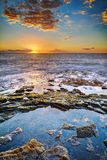 Zonsondergang over rotsachtige kustlijn Stock Foto