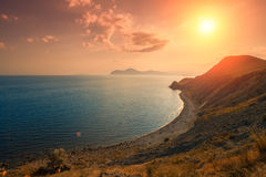 Zonsondergang over rotsachtige overzeese kust Royalty-vrije Stock Foto