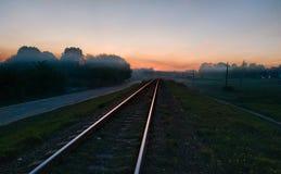 Zonsondergang over van de de zonsondergangschemering van Spoorwegsporen het gebied van het de aard hazefog gras stock foto