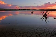 Zonsondergang over water stock afbeeldingen