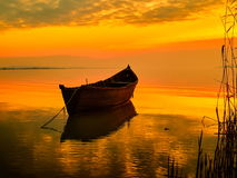 Zonsondergang over water en silhouet vissersboot Stock Foto's