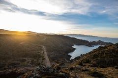 Zonsondergang over weg en overzeese klippen en lage wolken met duidelijke hemel royalty-vrije stock afbeelding