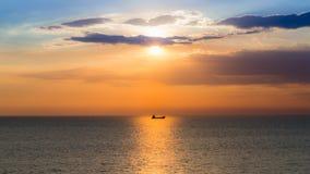 Zonsondergang over zeekust met kleine vissersboot Royalty-vrije Stock Foto's