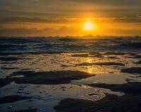 Zonsondergang in pools van water op het strand wordt weerspiegeld dat royalty-vrije stock foto