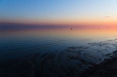 Zonsondergang in rode, blauwe, roze, gele kleuren op overzees Stock Foto