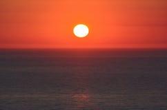 Zonsondergang, rode hemel en donkere overzeese oppervlakte Stock Fotografie
